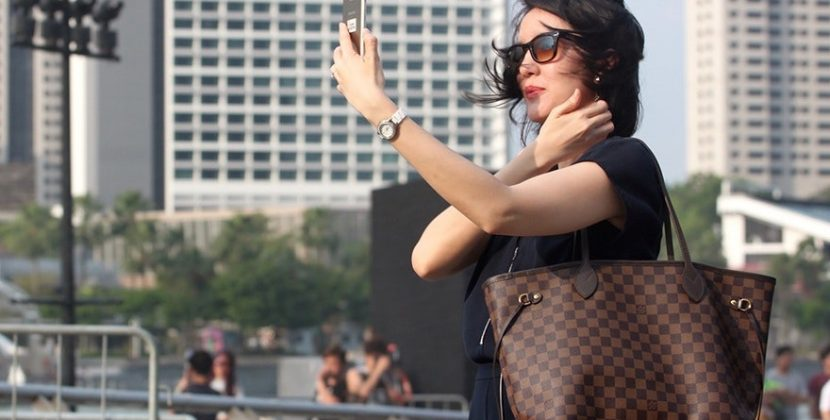 A girl wearing hand bag and taking selfie