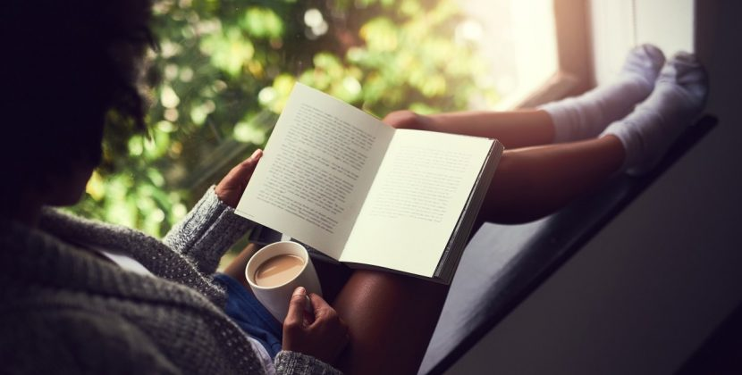 A girl reading a book and holding coffee cup