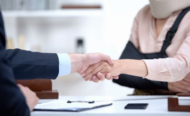 Insurance agent shaking hand with woman in arm sling, psychological suppor